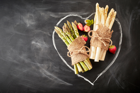 Seasonal fresh spring white and green asparagus spears tied in bundles with hessian laid on a hand drawn heart icon on textured slate with strawberries and copy space Reklamní fotografie