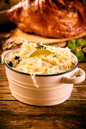 Bowl of sauerkraut cabbage in close up on wooden table Фото со стока - 101494742