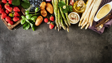 Healthy fresh spring fruit and vegetable border on textured slate with strawberries, blueberries, potatoes, basil and green and white asparagus shoots with Hollandaise sauce
