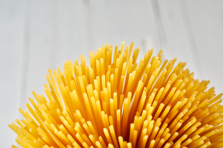 A close up of a golden, uncooked bundle of spaghetti on a high key background with copy space.