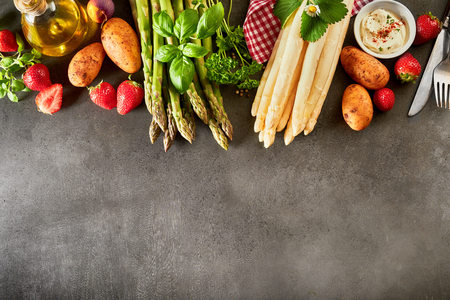 Selection of fresh fruit and veggies to accompany green and white spring asparagus spears arranged as a border with olive oil on a slate background with copy space Stock fotó - 101266916