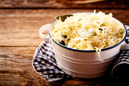 Bowl of sauerkraut cabbage on dishcloth against wooden table