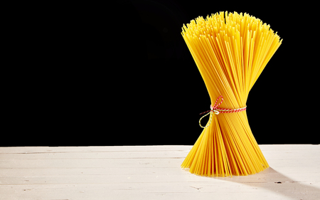 Golden spaghetti tied into a bunch with colourful string on a rustic timber table with a black background and copy space. 写真素材