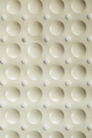 Surface of a pliable rubber bath mat with round dimples to provide traction and grip on wet surfaces while bathing in a full frame close up texture background Reklamní fotografie