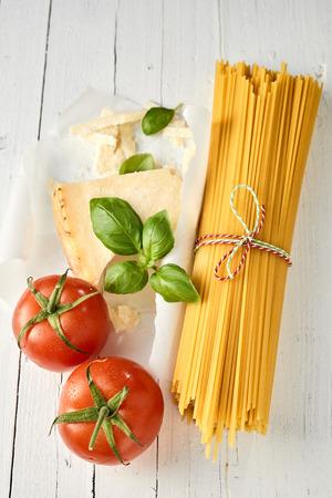 Dried Italian spaghetti with parmesan cheese, fresh ripe tomatoes and basil for preparing healthy Mediterranean cuisine