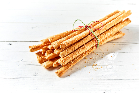 Bunch of grissini breadsticks tied with twine against white background