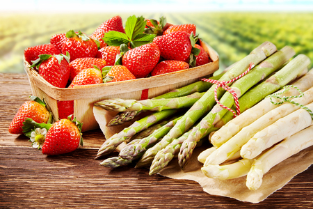 Fresh spring delicacies with white and green asparagus spears and a container of ripe red juicy strawberries outdoors on a farm or garden
