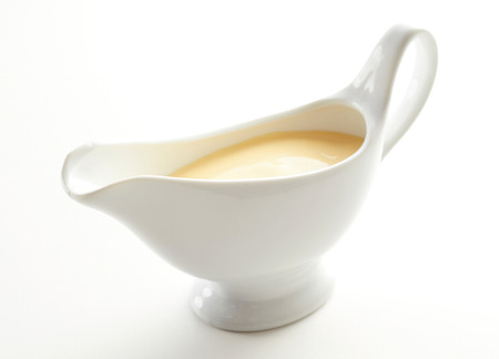 Sauce boat filled with creamy Hollandaise sauce made from melted butter, lemon juice, egg yolk whisked over a double boiler