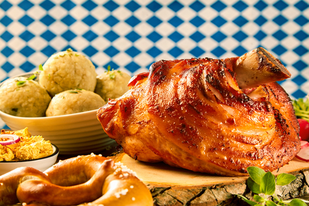 A crispy roasted pork knuckle served on a rustic wooden block with generous gourmet side dishes.