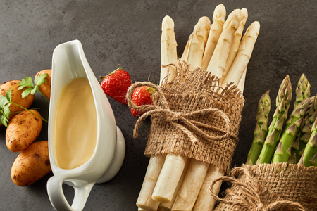 Tied bundles of fresh green and white asparagus spears with a sauce boat full of freshly prepared Hollandaise sauce, potatoes and strawberries on a slate background in an overhead view Фото со стока