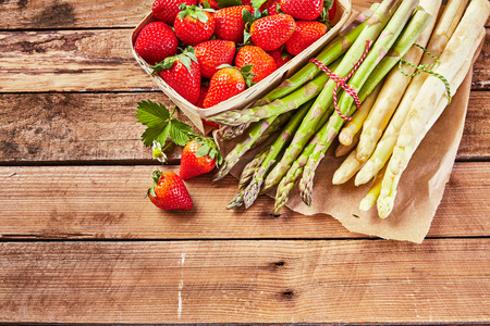 Bundles of fresh raw white and green asparagus spears with a small container of ripe juicy strawberries on a wooden table with copy space in a high angle view