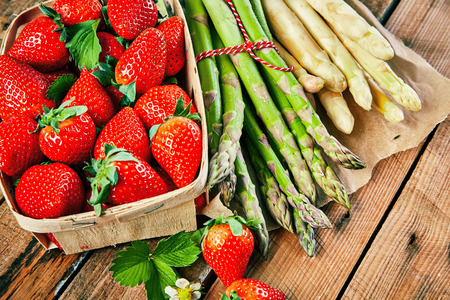 Box of fresh juicy red strawberries and bundles of white and green asparagus spears on a rustic wooden table in a close up view from above