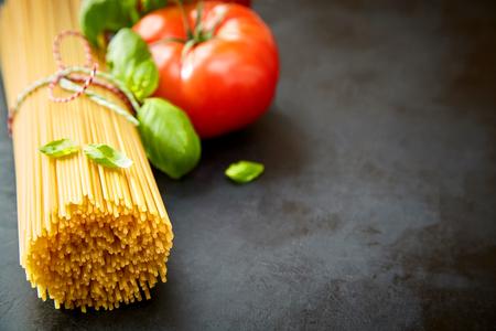 Bunch of raw spaghetti with tomato, basil on dark background