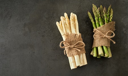 Bunches of fresh green and white asparagus spears tied with string and burlap on a slate background with copy space