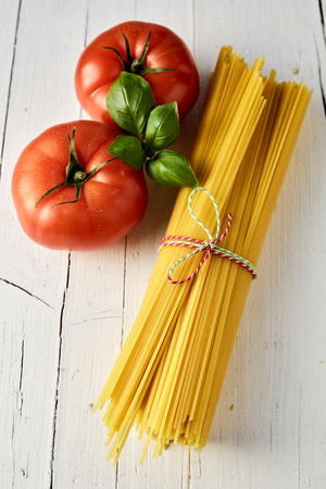 Bundle of dried spaghetti with fresh basil leaves and tomatoes for cooking Italian cuisine on a rustic white wood background
