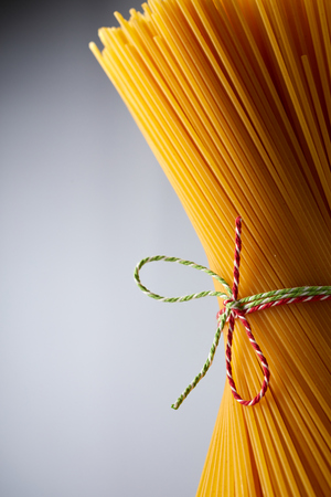 A close up of bundled, uncooked golden spaghetti tied up with colourful kitchen twine on a rustic background with copy space. 版權商用圖片