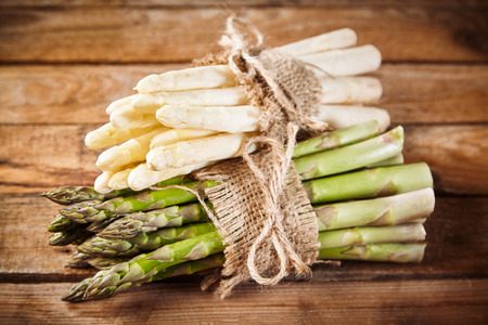 Spring harvest of fresh green and white asparagus spears tied with string and hessian on a rustic wood background