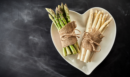 Fresh white and green asparagus tied with string and hessian on a heart-shaped white bowl on textured slate with copy space