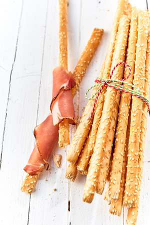 Grissini breadsticks wrapped in parma ham alongside a bundle tied with string on a white wooden table Banco de Imagens