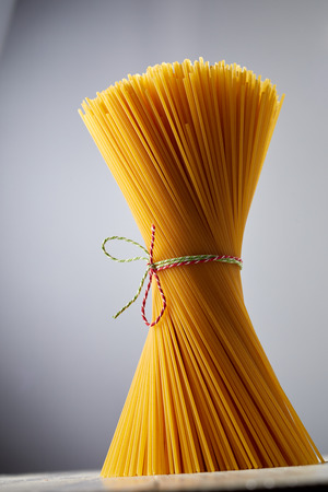 A close up of bundled, uncooked golden semolina spaghetti tied up with colourful kitchen twine on a rustic background with copy space.