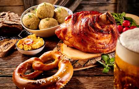Traditional German cuisine, Schweinshaxe roasted ham hock, pretzel, obatzter cheese spread with glass of pale beer on wooden table Stock Photo