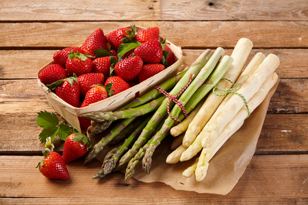 Fresh spring produce on a rustic wooden table with bundles of white and green asparagus spears and a punnet of ripe juicy strawberries 写真素材