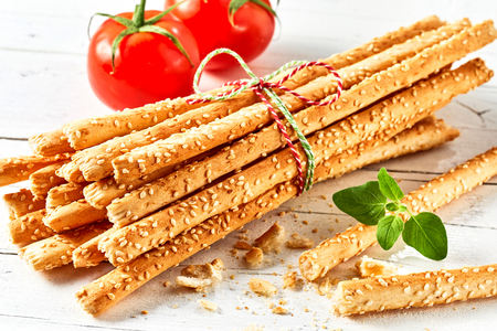 Bunch of grissini breadsticks with tomatoes on white background Stock Photo - 101294439