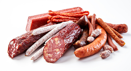 Display of a variety of seasoned spicy and smoked sausages with some cut through to show the texture of the meat on a white background in a low angle view