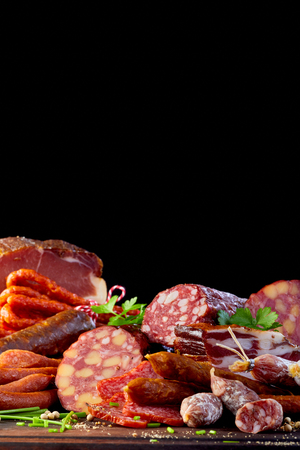 Assortment of spicy dried sausages and salami with chives and parsley on a wooden table with copy space above on black Reklamní fotografie