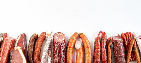 Panorama banner with a diversity of spicy dried, cured or smoked sausages arranged as a bottom border with copy space on white