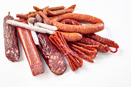 Large selection of different dried spicy seasoned beef and pork sausages on a white background for advertising or a menu Stock Photo