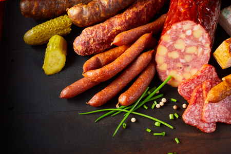 Assortment of speciality seasoned spicy sausages arranged in the corner on a dark background with chives, peppercorns, pickled cucumbers or gherkins and copy space