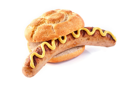 A seared barbecued sausage or bratwurst in a crusty bread bun with mustard on a white background with copy space. Stockfoto