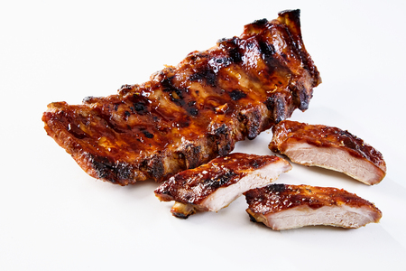 Barbecued and marinated sticky spare ribs on a white background with copy space. 版權商用圖片