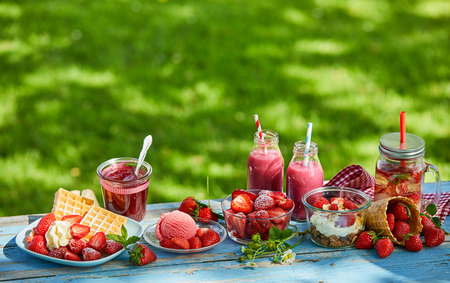Fresh, healthy, vibrant summer strawberry smoothie bowl, juices and desserts picnic on a bright outdoor table setting. Stock Photo