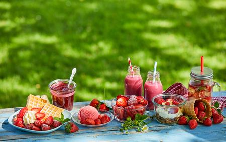 Frisse, gezonde, levendige zomerse aardbeiensmoothiekom, sappen en desserts picknick op een lichte buitentafel.