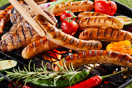 Summer barbecue with sizzling sausages and t-bone steaks cooking on a grill over a fire with fresh sweet peppers, chili, tomato and zucchini seasoned with rosemary