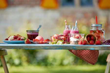 Fresh, healthy, colourful summer strawberries smoothie bowl, juices and desserts picnic on a bright outdoor table setting. Stock Photo