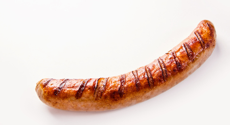 Side view of curved single German bratwurst sausage on white background.