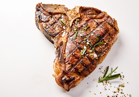 A succulent, grilled t-bone steak and herb garnish with a white background and copy space. Фото со стока