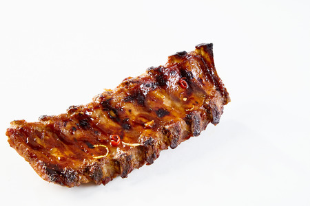 Barbecued and marinated sticky spare ribs on a white background with copy space. Standard-Bild
