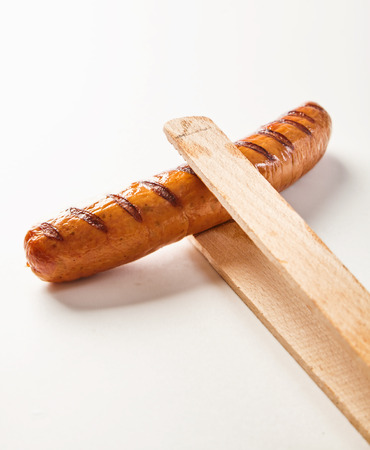 Wooden tongs holding a seared, barbecued Krakauer polish sausage on a white background with copy space. Stock fotó