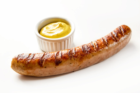 A seared barbecued sausage served with yellow mustard in a small ramekin with a white background and copy space. Banque d'images