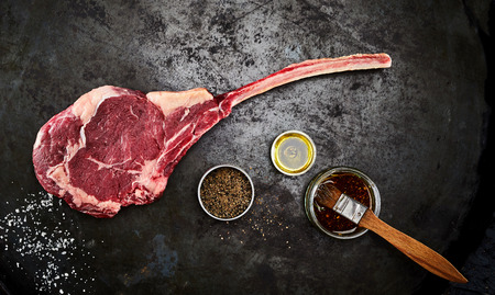 Tender raw trimmed bone-in ribeye steak with jars of marinade, spice rub an olive oil viewed from above on an old metal surface