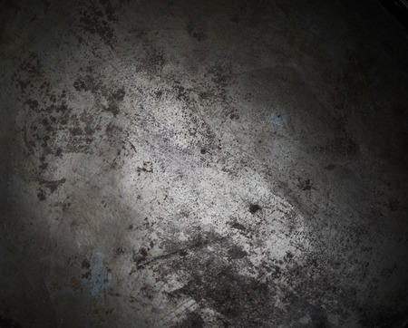 Background texture of blackened burnt metal on a vintage or rustic kitchen utensil with vignette and central highlight for copy space Stock Photo