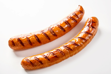 Two seared barbecue sausages on a white background with copy space.