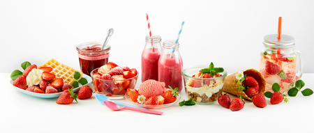 Strawberry themed panorama of fresh fruit recipes with waffles, puree, jam, salad, ice cream, muesli topped with berries and infused water over white Foto de archivo - 102243790