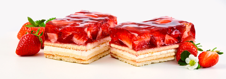Two slices of strawberry and cream layer cake or tart topped with fresh ripe fruit in a syrup in a panorama banner on white