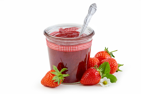 Jar of fresh strawberry jam or puree tied with checkered textile ribbon and surrounded by ripe berries isolated on white