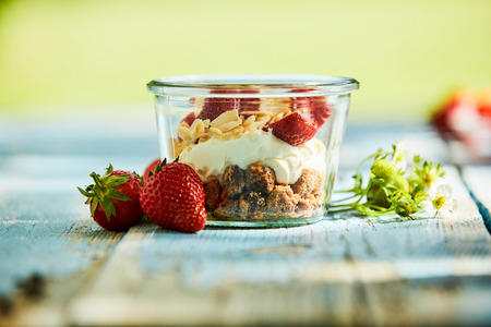 A fresh, healthy yoghurt, strawberry and muesli smoothie bowl on a rustic table setting.